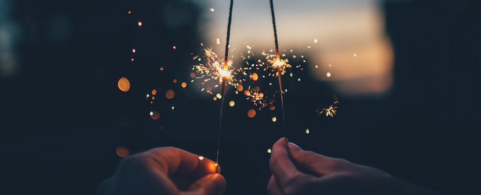 Individual holding 2 firecrackers in each hand, against a night background